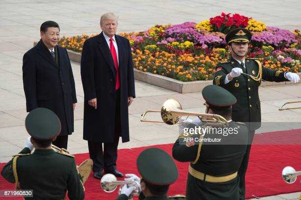 China's President Xi Jinping and US President Donald Trump attend a welcome ceremony at the Great Hall of the People in Beijing on November 9 2017...