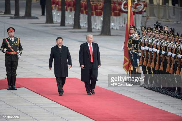 China's President Xi Jinping and US President Donald Trump review Chinese honour guards during a welcome ceremony at the Great Hall of the People in...