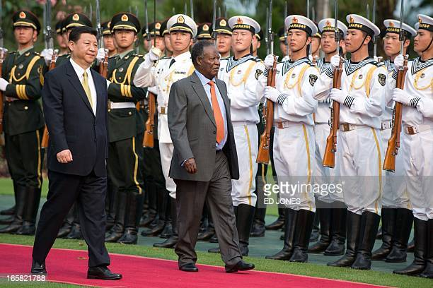 China's President Xi Jinping and Zambia's President Michael Sata review an honour guard during a welcoming ceremony in Sanya on the southern Chinese...