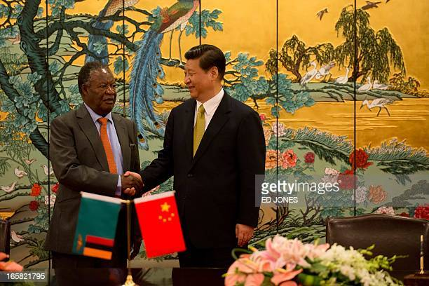 China's President Xi Jinping and Zambia's President Michael Sata shakes hands following a signing ceremony in Sanya on the southern Chinese resort...