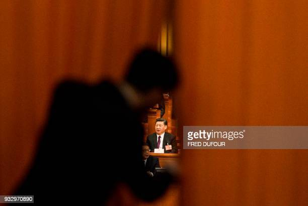 China's President Xi Jinping appears between curtains after he was elected for a second term during the fifth plenary session of the first session of...