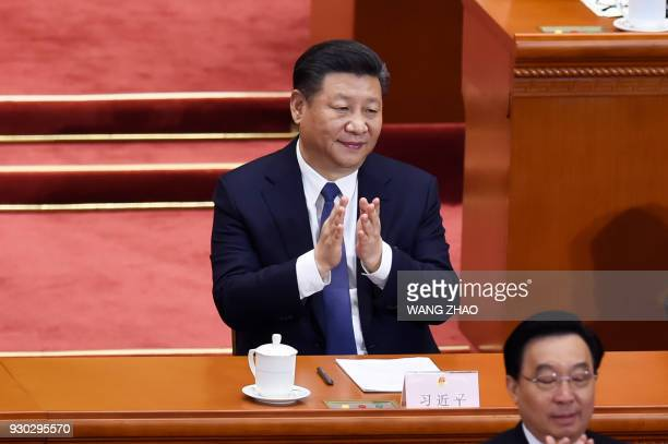 TOPSHOT China's President Xi Jinping applauds after the voting result are announced during the third plenary session of the first session of the 13th...