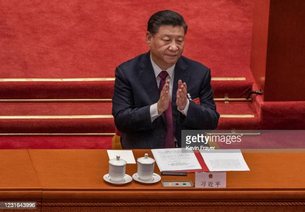 China's President Xi Jinping applauds after voting during a session that also included a vote in favour of a resolution to overhaul Hong Kong's...