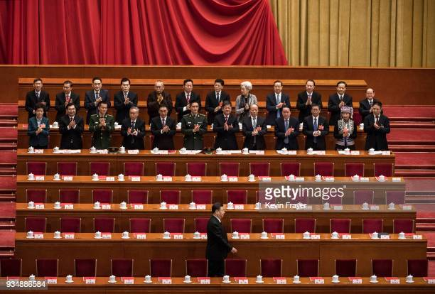 China's President Xi Jinping bottom is applauded as he arrives to the closing session of the National People's Congress at The Great Hall Of The...