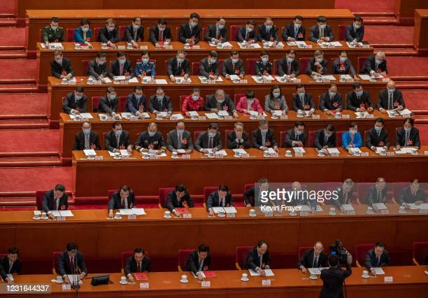 China's President Xi Jinping, bottom left, and other senior leaders and lawmakers press buttons while voting on a resolution during a session that...