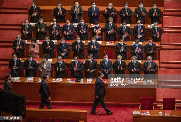 China's President Xi Jinping, bottom right, and Premier Li Keqiang, bottom left, are applauded by lawmakers as they arrive for the closing session of...
