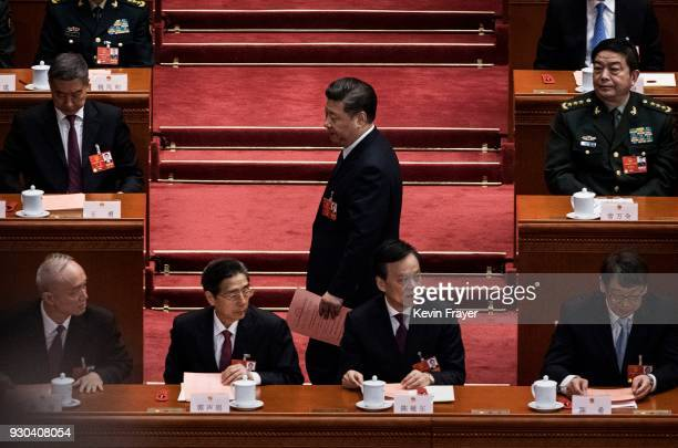 China's President Xi Jinping carries his ballot as he walks to vote on an amendment to the constitution during a session of the National People's...