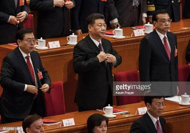 China's President Xi Jinping center adjusts his jacket after his speech to the closing session of the National People's Congress at The Great Hall Of...