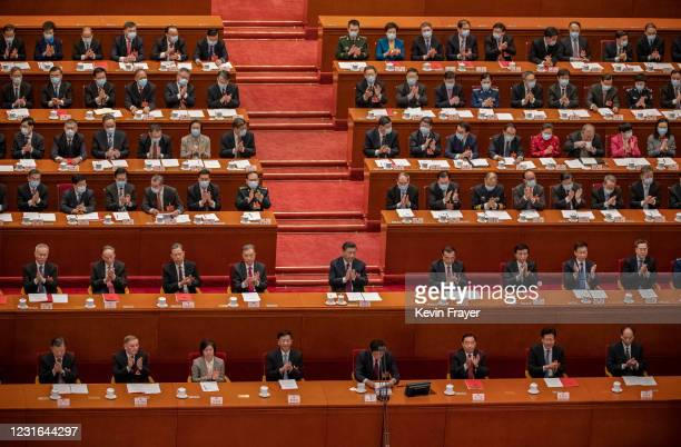 China's President Xi Jinping, center, and lawmakers applaud after voting during a session that also included a vote in favour of a resolution to...