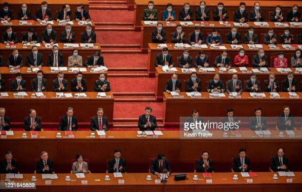 China's President Xi Jinping, center, and lawmakers applaud after voting in favour of a resolution to overhaul Hong Kong's electoral system, during...