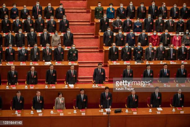China's President Xi Jinping, center, and lawmakers stand for the anthem during the closing session of the National People's Congress at the Great...