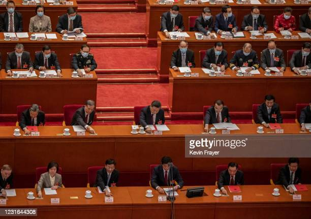 China's President Xi Jinping, center, and Premier Li Keqiang, center right, and other senior leaders press a button to vote in favour of a resolution...