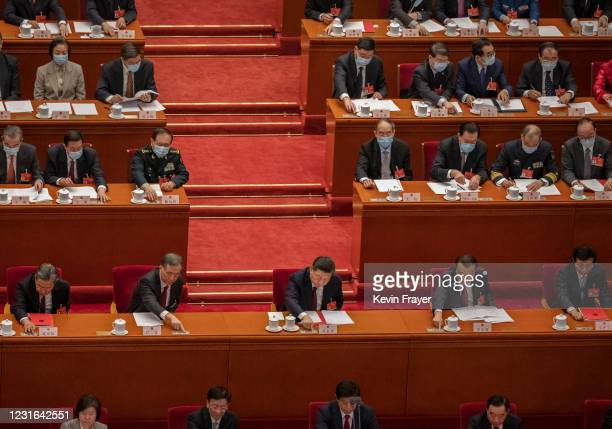 China's President Xi Jinping, center, and Premier Li Keqiang, right, and other senior leaders press a button to vote in favour of a resolution to...