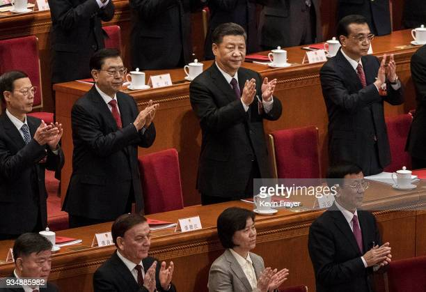 China's President Xi Jinping center applauds as he stands next to Premier Li Keqiang right and others after his speech to the closing session of the...
