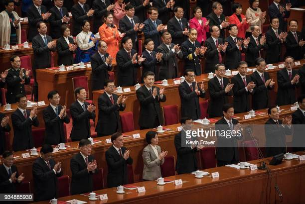 China's President Xi Jinping center applauds with others after his speech to the closing session of the National People's Congress at The Great Hall...