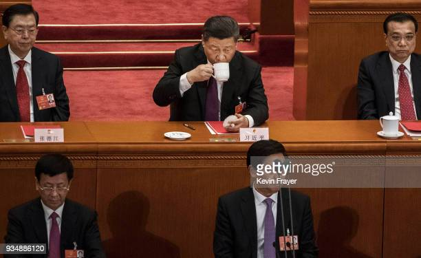 China's President Xi Jinping center drinks tea during the closing session of the National People's Congress at The Great Hall Of The People on March...
