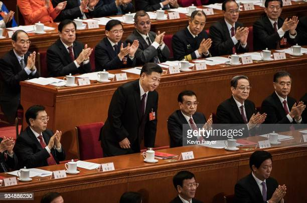 China's President Xi Jinping center is applauded by Premier Li Keqiang centre right and others as he takes his seat after his speech to the closing...