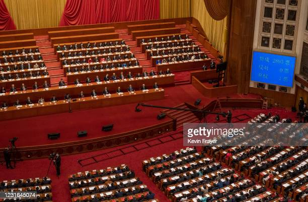 China's President Xi Jinping, center left, and lawmakers gather as the result of a vote in favour of a resolution to overhaul Hong Kong's electoral...