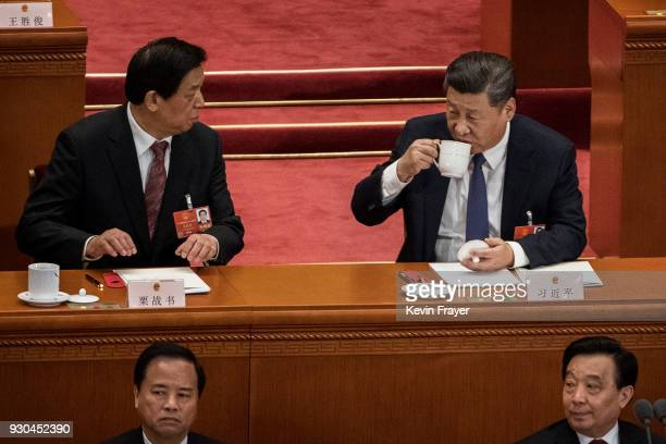 China's President Xi Jinping drinks tea after voting at a session of the National People's Congress on a constitutional amendment at The Great Hall...