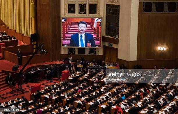 China's President Xi Jinping is seen on a large screen over delegates as he joins a session of the National People's Congress to vote on a...