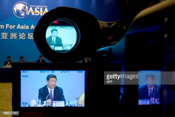 China's President Xi Jinping is shown on the screens of a TV camera during his meeting with representatives of entrepreneurs at the annual Boao Forum...