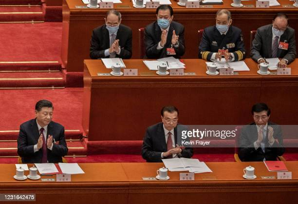 China's President Xi Jinping, left, and Premier Li Keqiang, bottom center, and other senior leaders applaud after a vote in favour of a resolution to...