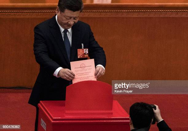 China's President Xi Jinping places his ballot in a box during a vote on an amendment to the constitution during a session of the National People's...