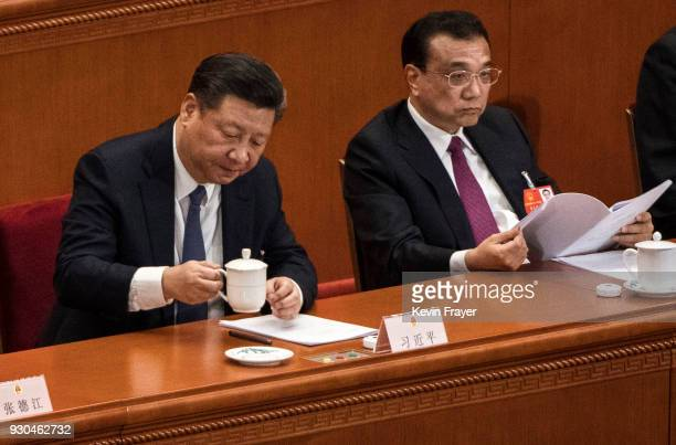 China's President Xi Jinping prepares to drink tea as he sits next to Premier Li Keqiang after voting at a session of the National People's Congress...