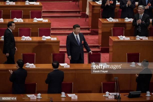 China's President Xi Jinping prepares to take his seat at a session of the National People's Congress to vote on a constitutional amendment at The...