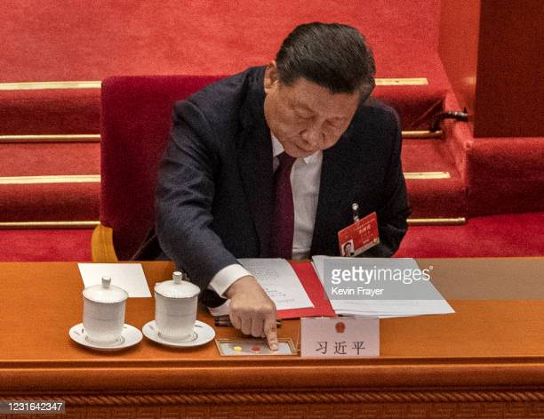 China's President Xi Jinping presses a button to vote in favour of a resolution to overhaul Hong Kong's electoral system, that was approved during...