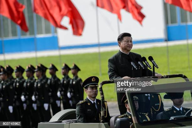 China's President Xi Jinping reviews troops from a car at a garrison of the People's Liberation Army in Hong Kong on June 30 2017 Tanks missile...