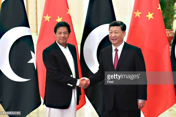 China's President Xi Jinping, right, shakes hands with Pakistan's Prime Minister Imran Khan before a meeting at the Great Hall of the People on April...