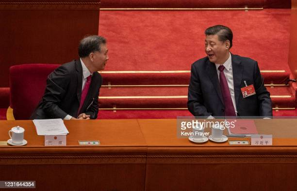 China's President Xi Jinping, right, talks with Politburo member Wang Yang , left, during the closing session of the National People's Congress at...