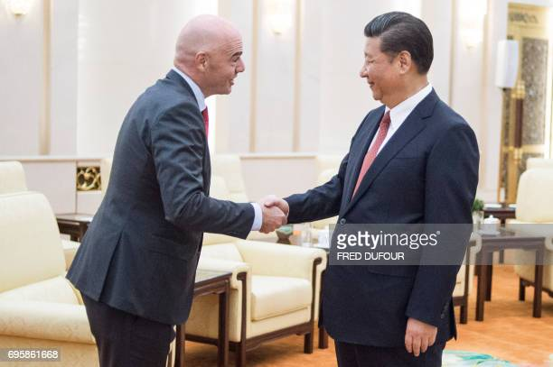 China's President Xi Jinping shakes hands with FIFA President Gianni Infantino at the Great Hall of the People in Beijing on June 14 2017 Chinese...