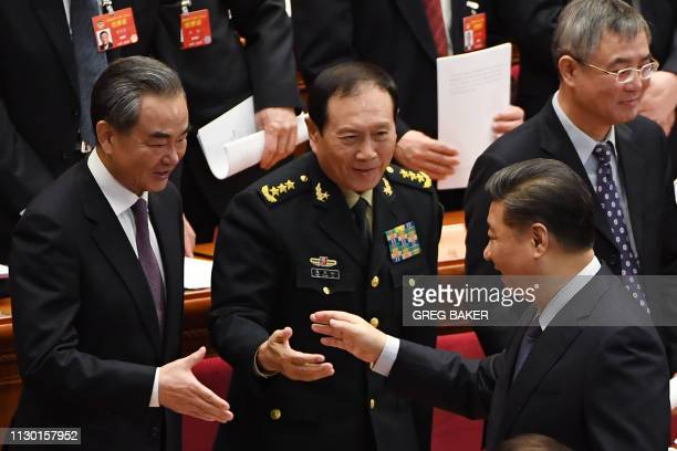 China's President Xi Jinping shakes hands with Foreign Minister Wang Yi and Defence Minister Wei Fenghe as they leave after the closing session of...