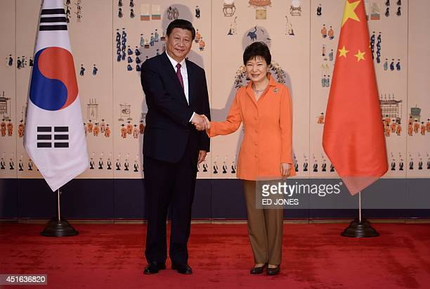 China's President Xi Jinping shakes hands with his South Korean counterpart Park GeunHye prior to a summit meeting at the Blue House in Seoul on July...