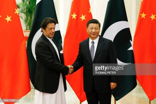 China's President Xi Jinping shakes hands with Pakistan's Prime Minister Imran Khan ahead of their meeting at the Great Hall of the People in Beijing...