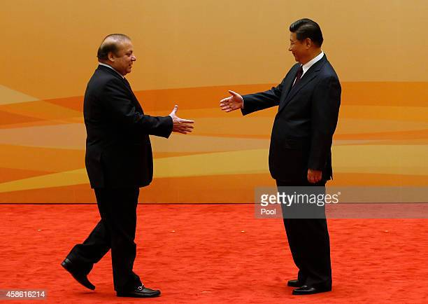 China's President Xi Jinping shakes hands with Pakistan's Prime Minister Nawaz Sharif at their family photo session prior to the Dialogue On...