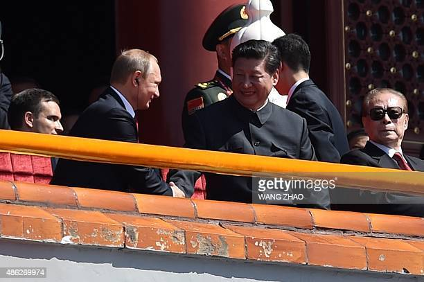 China's President Xi Jinping shakes hands with Russia's President Vladimir Putin during a military parade in Tiananmen Square in Beijing on September...