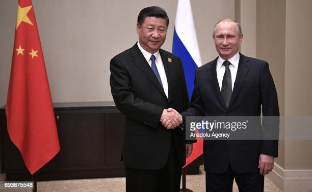 China's President Xi Jinping shakes hands with Russia's President Vladimir Putin as they meet for talks ahead of a meeting of the Shanghai...