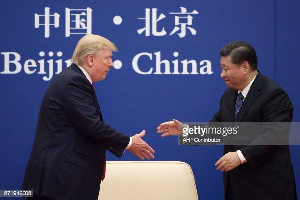 China's President Xi Jinping shakes hands with US President Donald Trump during a business leaders event at the Great Hall of the People in Beijing...