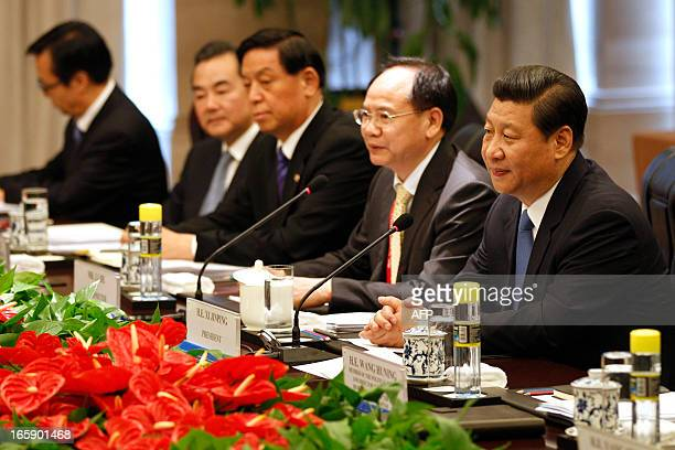 China's President Xi Jinping sits with his delegation as he listens to Cambodia's Prime Minister Hun Sen during their meeting on the sidelines of the...
