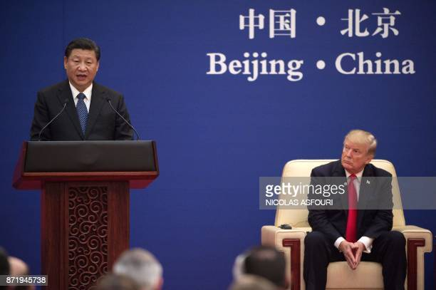China's President Xi Jinping speaks next to US President Donald Trump during a business leaders event at the Great Hall of the People in Beijing on...