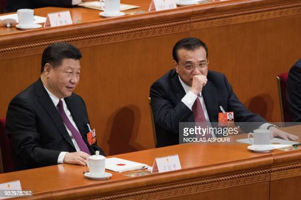 China's President Xi Jinping speaks with Premier Li Keqiang during the fifth plenary session of the first session of the 13th National People's...