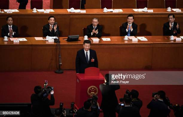 China's President Xi Jinping stands after placing his ballot in a box during a vote on an amendment to the constitution during a session of the...