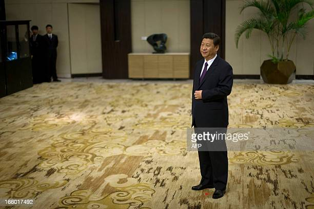 China's President Xi Jinping stands in his position marked by a red star on the carpet while he waits to shake hands with representatives of...