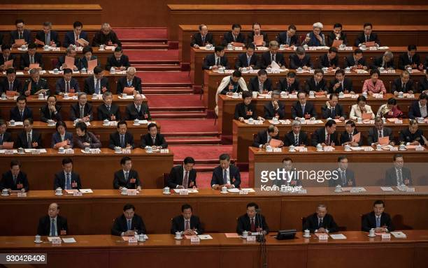 China's President Xi Jinping talks with Li Zhanshu as they examine their before a vote on an amendment to the constitution during a session of the...
