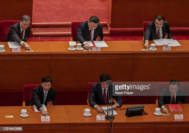 China's President Xi Jinping, top center, and Premier Li Keqiang, right, and other senior leaders press a button to vote in favour of a resolution to...