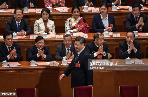 China's President Xi Jinping walks back to his seat after casting his ballot on an amendment to the constitution during a session of the National...