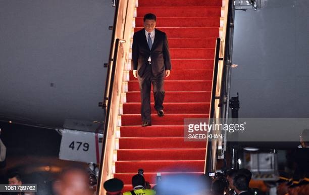 China's President Xi Jinping walks down the stairs of his plane upon arrival at Port Moresby International Airport on November 15 ahead of...